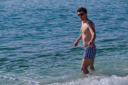 portrait of a young handsome man 25-30 years old on the background of the sea surface. In sunglasses, with a naked torso, brunette with thick hair