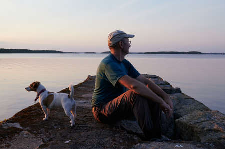 middle-aged man sits with a Jack Russell dog on a stone mall, enjoys the seascape, the pet looks the other way. Summer, evening, soft sunset lighting. Standard-Bild