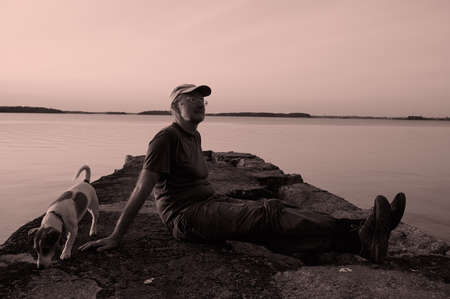 middle-aged man sits with a Jack Russell dog on a stone mall, enjoys the seascape, the pet looks the other way. Summer, evening, soft sunset lighting.