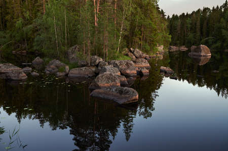 typical Finnish landscape - a lake in a pine forest with huge boulders brought here during the Ice Age. Evening, dim light, strongly diffused lighting, selective focus.