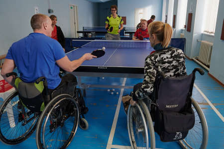 SAINT PETERSBURG, RUSSIA - FEBRUARY 11, 2021: Wheelchair users lead an active lifestyle, play table tennis, the moment of the game, ball serve Sajtókép