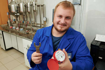 Saint Petersburg, Russia - September 16, 2020: An engineer works in a laboratory at a special high-tech stand for testing and testing new and used cold and hot water meters