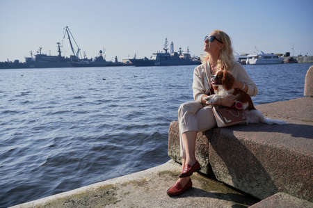 A young blonde woman in light casual clothes walks with a Cavalier King Charles Spaniel dog in the historical center of the small town of Kronstadt on a sunny fine day along the cobblestones