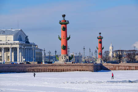 Saint Petersburg, Russia - March 4, 2019: View of the rostral columns in winter, a man went out on the ice along the frozen Neva, an architectural landmark of the city Sajtókép