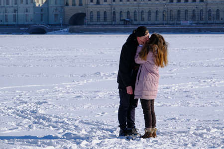 Saint Petersburg, Russia - March 4, 2019: Young people in the middle of the frozen Neva River and the sights of the city, hugging and looking at each other in love.