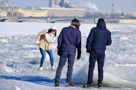 Saint Petersburg, Russia - March 4, 2019: People on a frosty winter day walk on the ice of the Neva River and see the sights of the city,