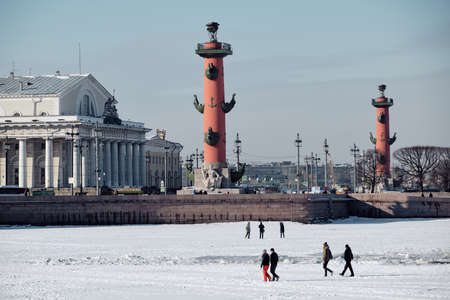 St. Petersburg, Russia - March 4, 2019: View of the Rosstral Columns - the main attraction of the city, tourists inspect the architecture from the ice of the Neva