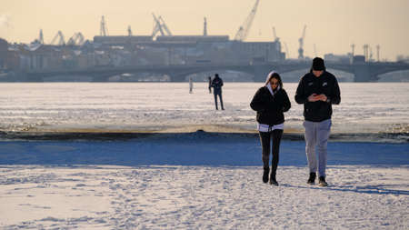 Saint Petersburg, Russia - March 4, 2019: People walk on the ice of the frozen Neva River and put themselves in danger, in the city center, against the backdrop of attractions