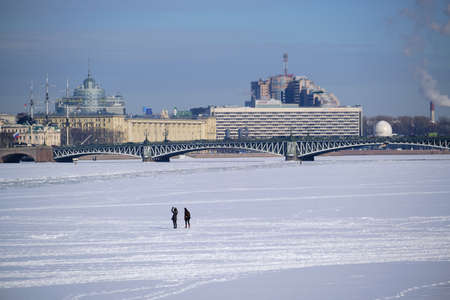 Saint Petersburg, Russia - March 4, 2019: View of the Trinity Bridge in winter, a man went out on the ice along the frozen Neva, an architectural landmark of the city