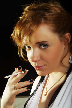beautiful woman with cigarette on dark background photo