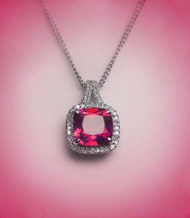 ruby stone: red diamond necklace on pink surface Stock Photo