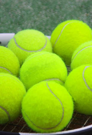 tennis racket with balls on court photo