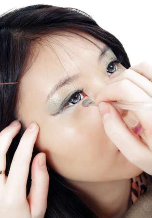 asian girl applying make up photo