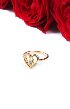 wedding ring with rose over white surface photo