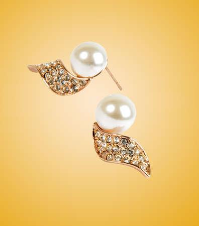 ear rings: golden ear rings on yellow surface