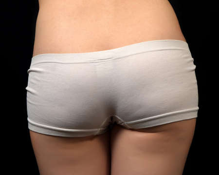 woman buttocks with pants on dark photo