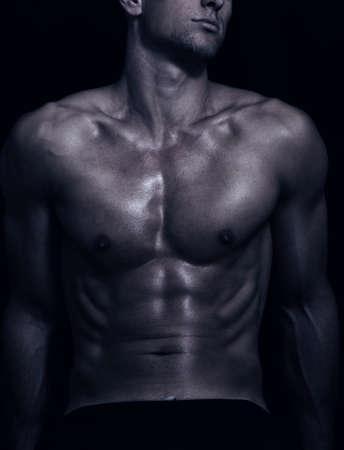 niño sin camisa: forma del cuerpo masculino deportivo en la oscuridad