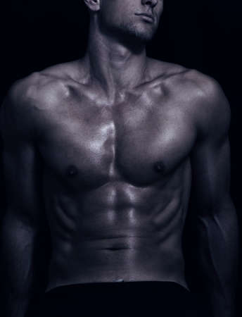 body builder: shape of sporty male body on dark