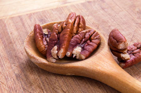 whole pecans: healthy nuts over wooden spoon