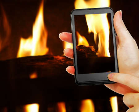 phone in hand with fireplace picture photo