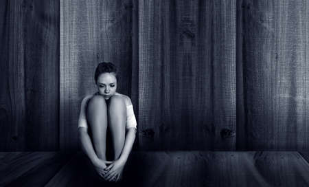 woman sitting on floor: depressed girl sitting near the wall Stock Photo
