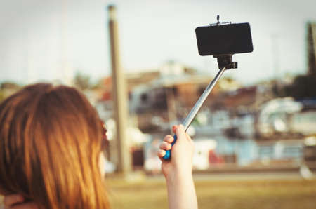 stick: girl taking selfie picture outdoors