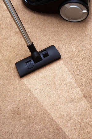 dirty house: closeup of the vacuum on the carpet