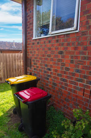 big bin: old style  brick house with garbage bins Stock Photo