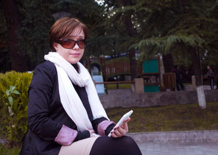 outoors: casual woman with phone outoors Stock Photo