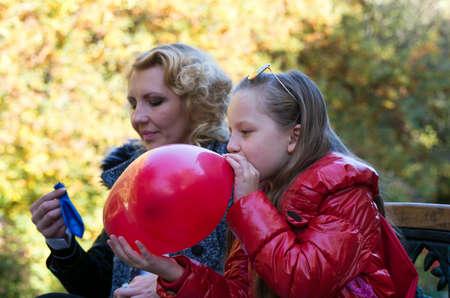 niños rubios: madre e hija en el parque de otoño con globos