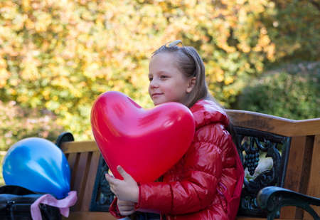 niños rubios: chica bonita en el parque de otoño con globos