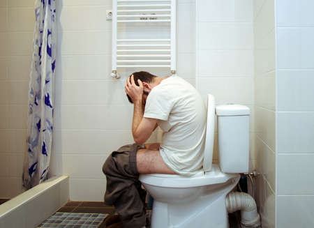 constipated: man having problems in toilet Stock Photo