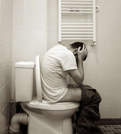 man having problems in toilet Stock Photo