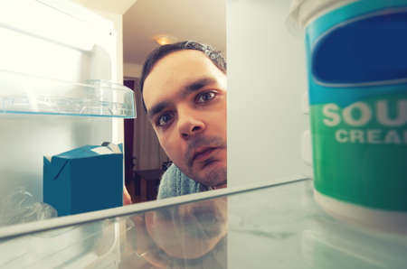 refrigerador: hombre hambriento con la cara divertida abre la nevera