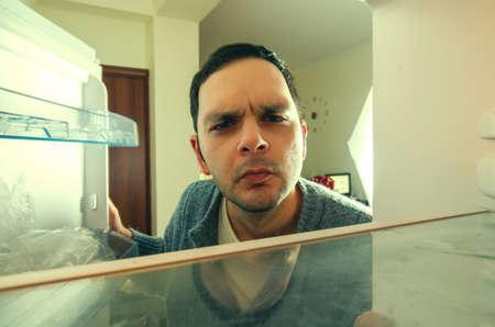 재미 있은 얼굴을 가진 배고픈 남자는 냉장고를 엽니 다