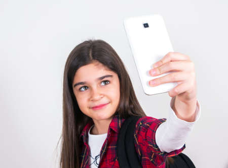 one child: pretty schoolgirl with bag and phone taking selfie Stock Photo