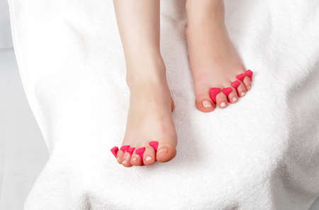 spa pedicure: female legs in salon getting pedicure