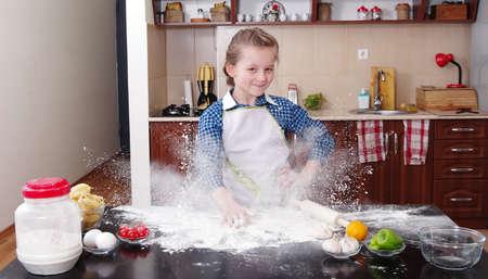klein meisje helpt om te bakken in een rommelige keuken
