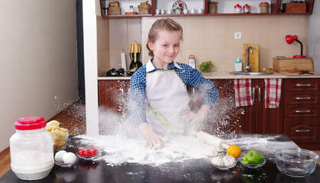 little girl is helping to bake  in a messy  kitchen Reklamní fotografie - 53921218