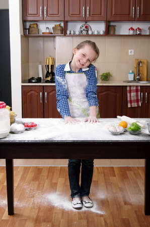 messy kitchen: little girl is helping to bake  in a messy  kitchen