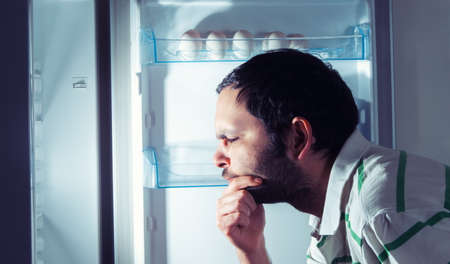 refrigerator: funny man looking into refrigerator Stock Photo
