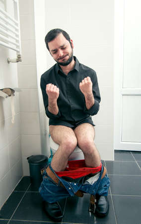 intestinal problems: man having problems in the toilet