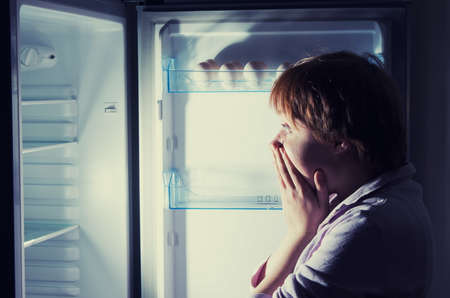 hungry: shocked woman looking into refrigerator Stock Photo