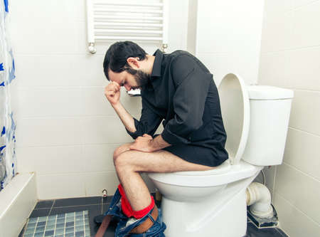 constipated: man having problems in the toilet