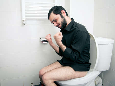 man having problems in the toilet