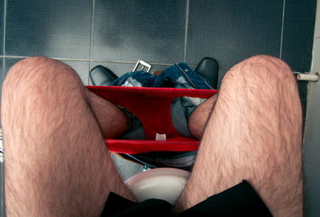 constipated: male legs in the toilet Stock Photo