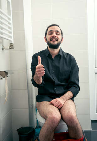 constipated: funny man in the toilet Stock Photo