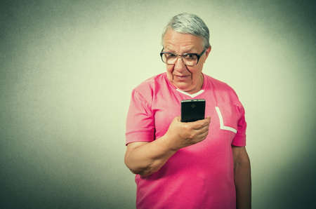 unknown age: portrait of the funny senior woman  looking on phone Stock Photo