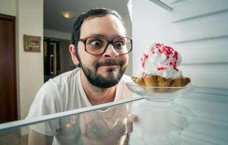 hombre divertido ve el pastel dulce en la nevera Foto de archivo