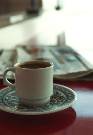 Cup of coffee with newspaper in cafe